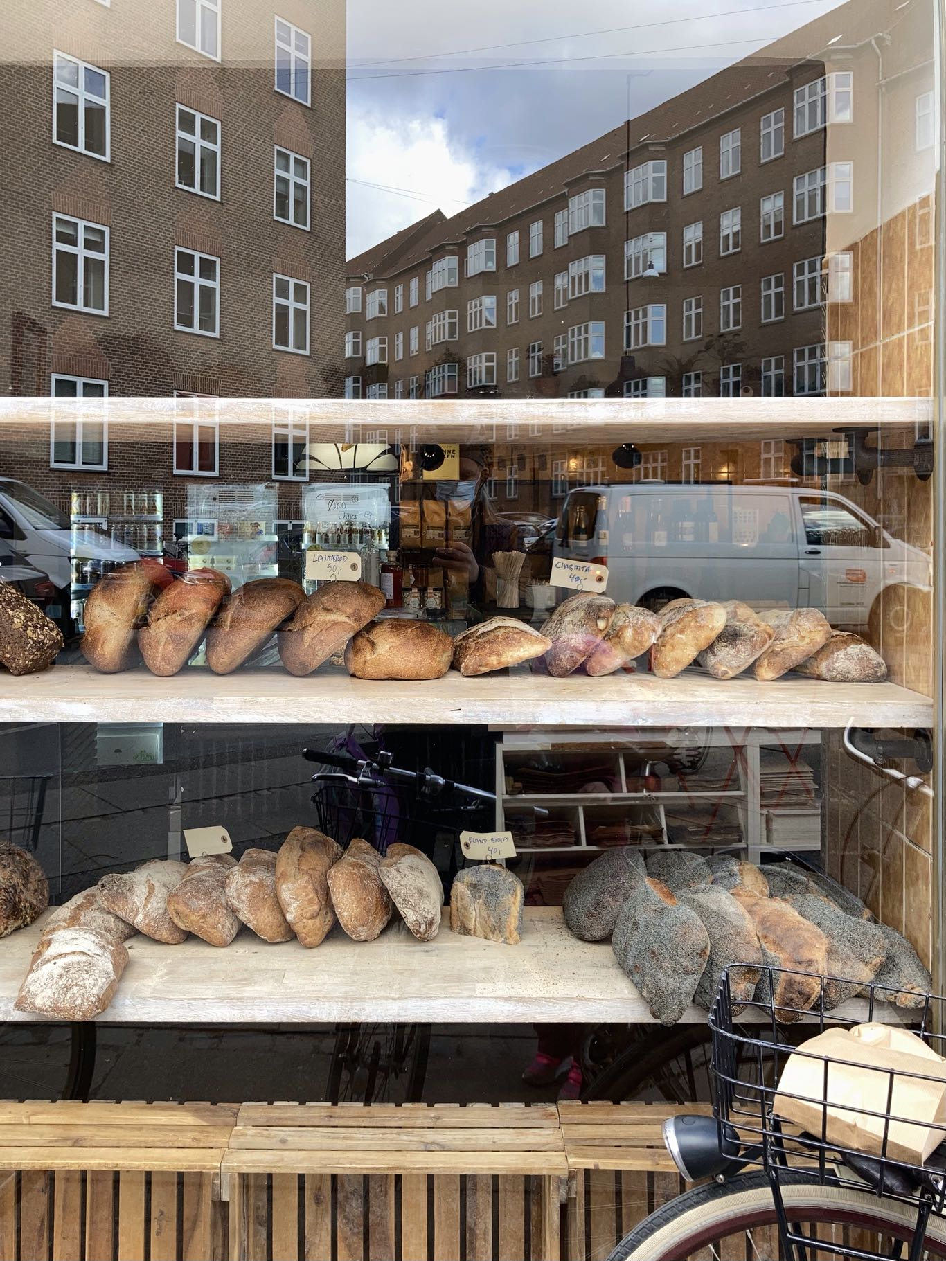 Looking through the window of 'Vores Brød', our local bakery, as we waited our turn (only two allowed in at a time). The sun a little behind the clouds as I took the picture, so there's not too much of my reflection in the window, but still managed to catch the van driving by. Fully organic, all sourdough. Very nice people. It's actually not our daily bread, but at least once a week it's great to get some of their goodies (the pastries are wonderful too).