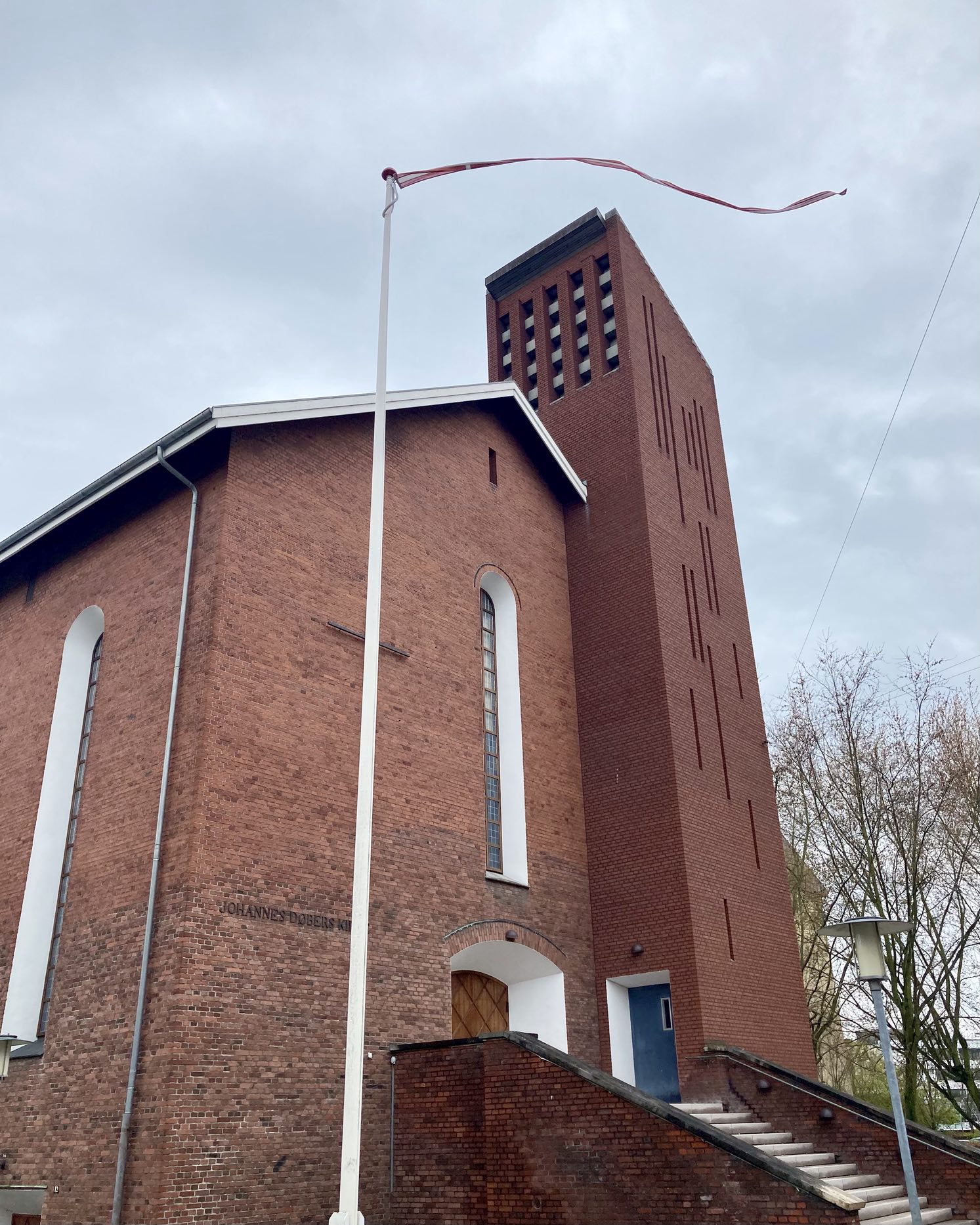 This was one of the photographs that I 'tried' with less today, but the one that spoke to me the most. The flag in the wind flowing over the modernistic church tower, grey skies behind it all. With freshly painted white windows and flagpole to give it all some extra definition. And a blue door.
