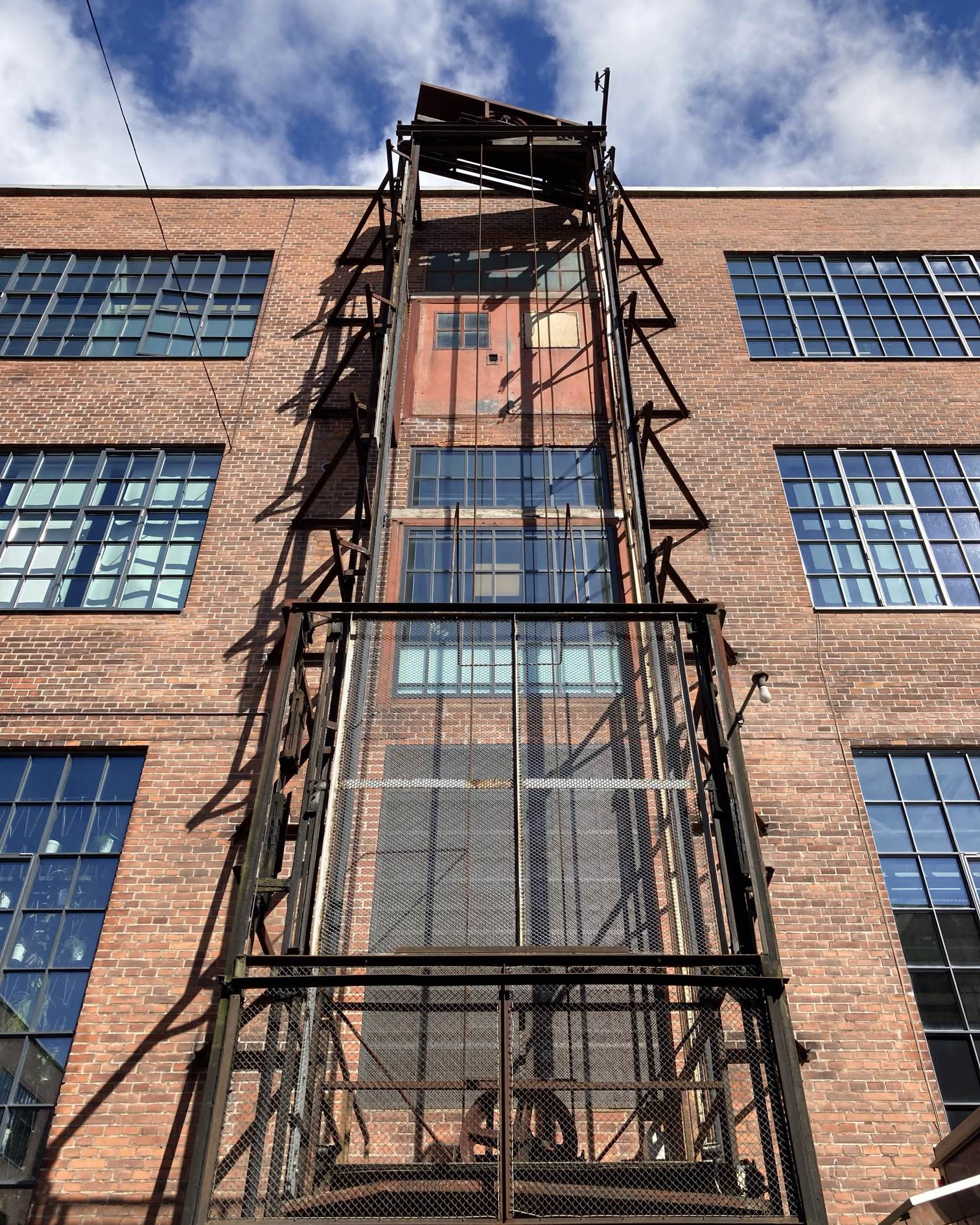A seldom seen external elevator on the outside of the old factory building that now houses the Bjarke Ingels Group offices. Afternoon sun. A few moments of blue sky and patchy clouds on what was an otherwise rainy day.