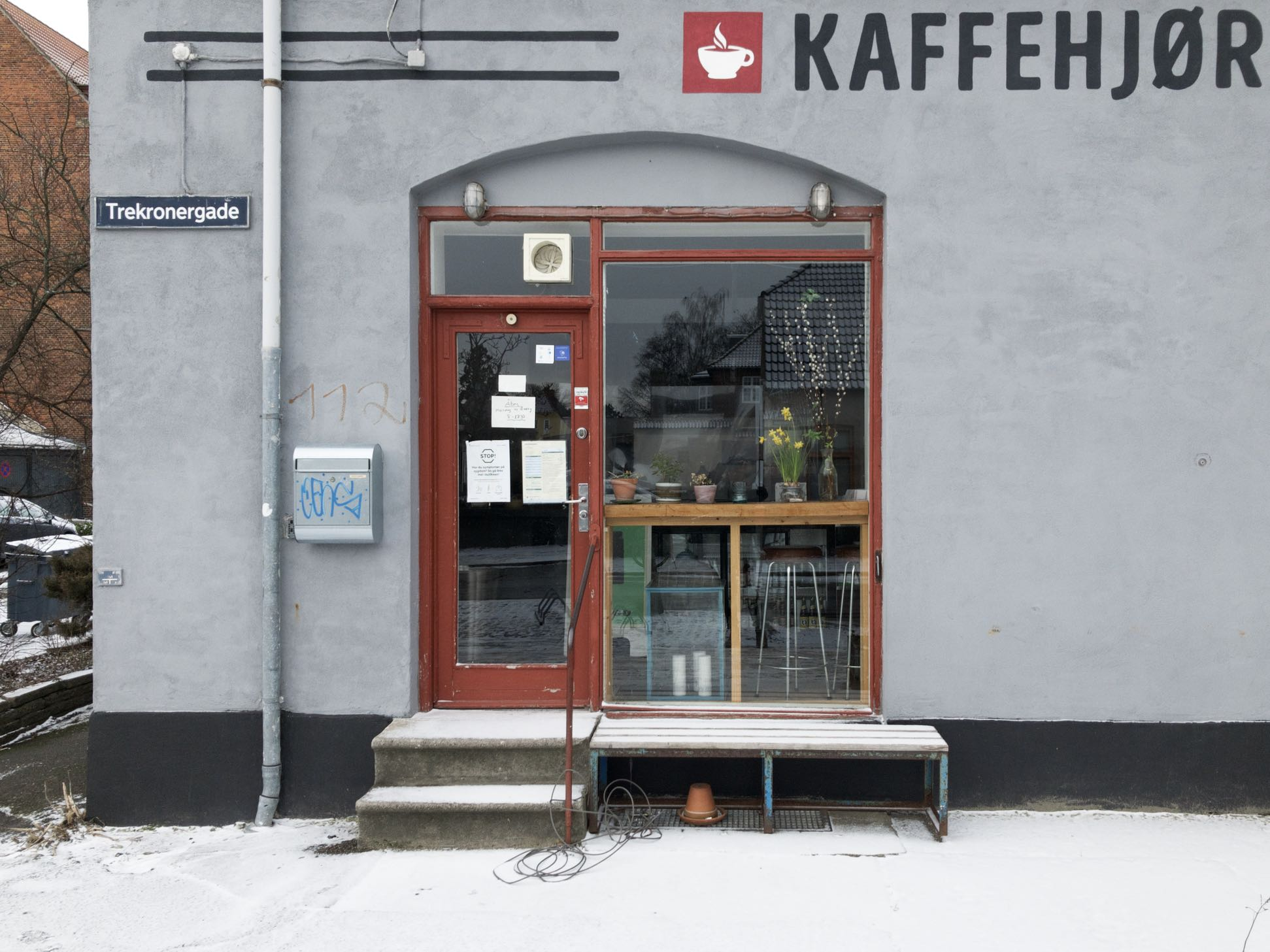Coffee corner in the snow. Corona notices in the window. Closed for business. The bench outside on a leash. Graffiti on the letterbox.