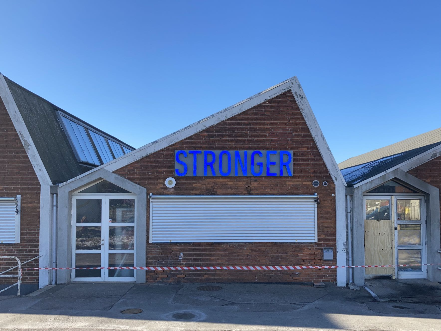 STRONGER – in deep neon blue, echoed in a purer framing sky. On a building that's somewhat challenged, cordoned off with red and white-striped tape.