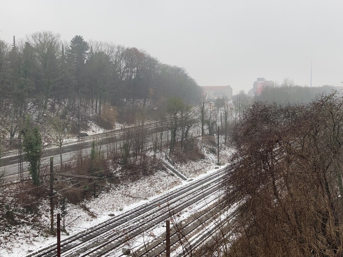 View from the bridge with snow on the tracks. Headlights from the light traffic on the road behind them. Mist in the air. pale colours and the thin blue chimney of the restaurant school reaching up in the distance.