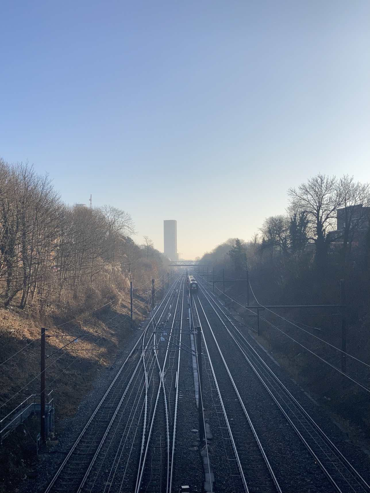 Train tracks, in shadow, from Valby bridge. The Carlsberg tower, slightly shrouded in the haze in the distance. Naked trees against an otherwise clear sky.
