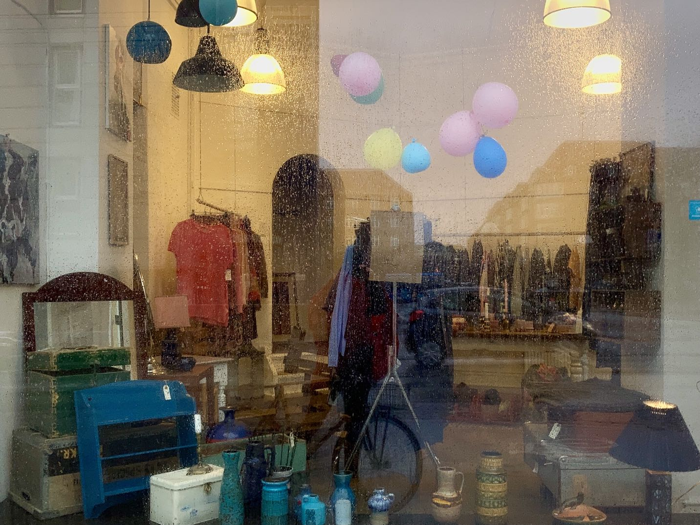 The rain-splashed window of a second hand store.