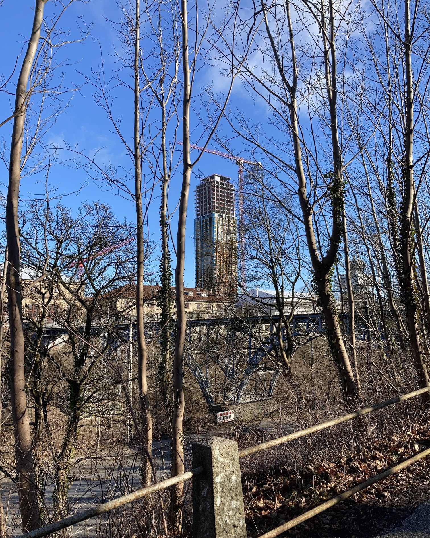 Through the trees, across the road, a view of the three-quarter-clad tower. Crisp blue sky. A bridge.  Old stone holding old metal pathway railing pipes.