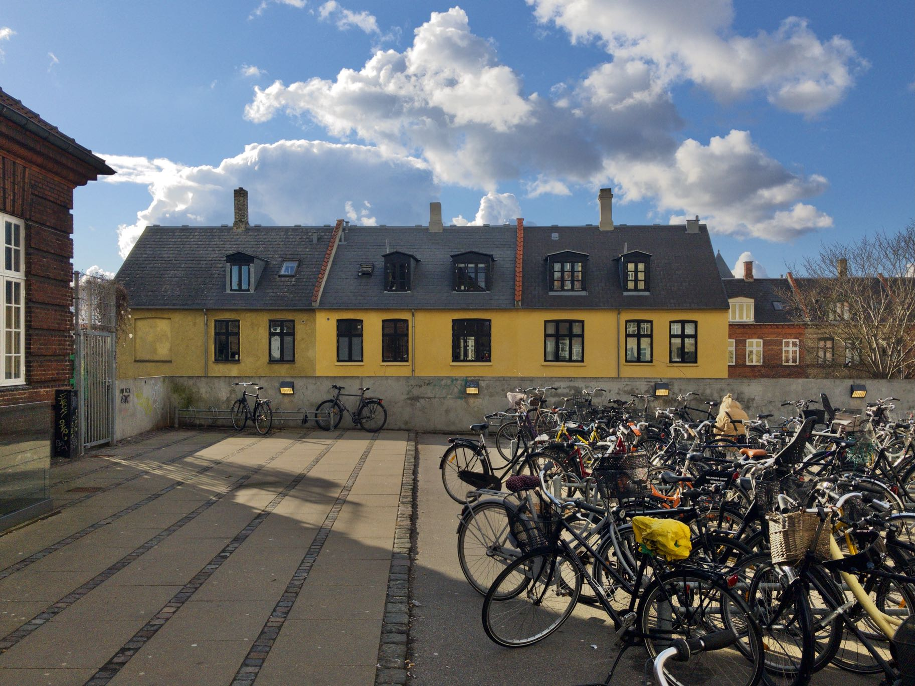 Valby station. A yellow building. Bicycles. Clouds. Had to dig into the RAW file to get the exposure of the clouds to work.