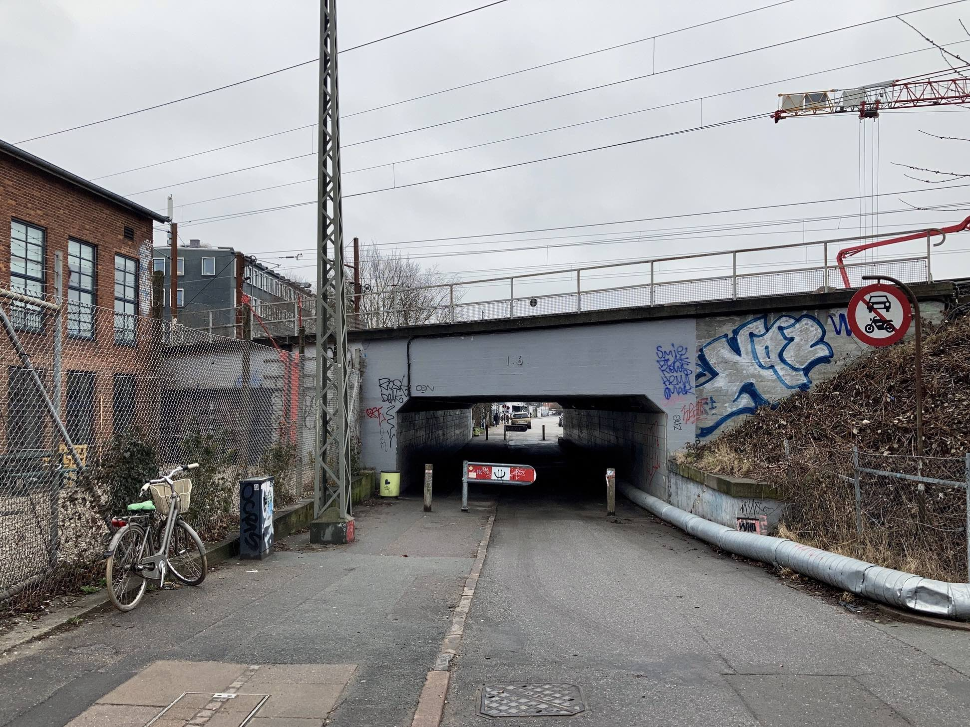 Tunnel under the tracks on a grey Monday morning. A bicycle. Chain fence. Smiling face on the restriction thingy. Graffiti. Dented pipe on the ground. Red outline of the no cars or motorcycles sign.