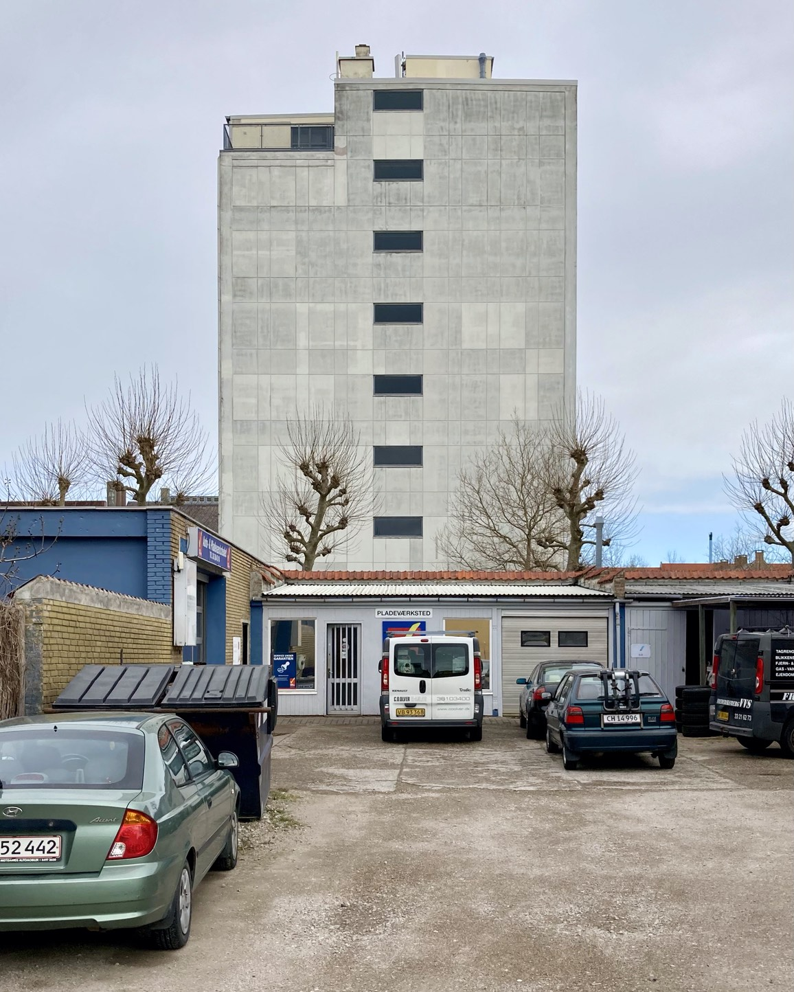 (Auto &) Pladeværksted: Car mechanic courtyard with the concrete of the Lundbeck building looming up behind it – mechanics for the human body. With strange hairy Van Gogh trees in the whatever-mans-land between them.