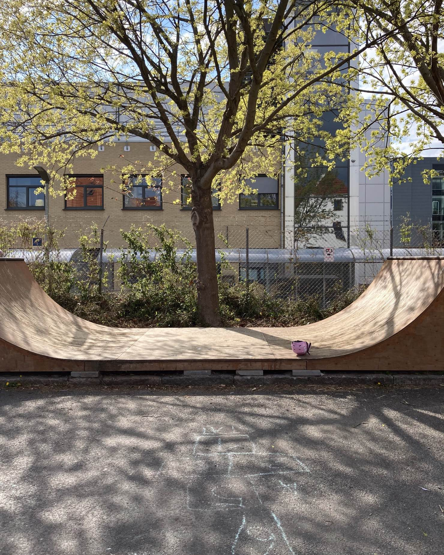 Skateboard ramp. Under a tree. Shadows from the tree. Hopscotch on the asphalt in front of it. Afternoon sun.
