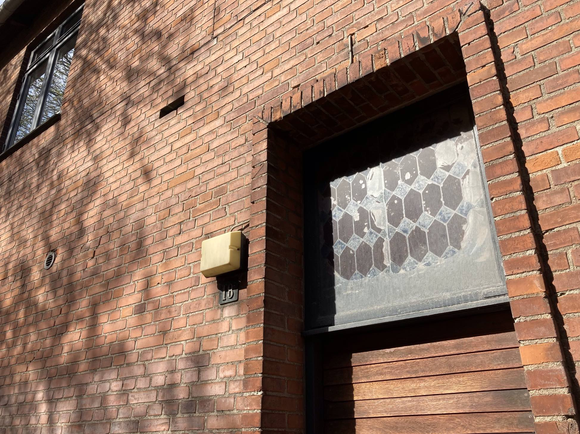 A little stained glass window, unexpected in the doorway of an old factory building, peeking out from behind the grime. Shadow play on the surrounding brick – one of them missing. An off-yellow door light. A ventilation hole. An expressionist angle after all my straightness.