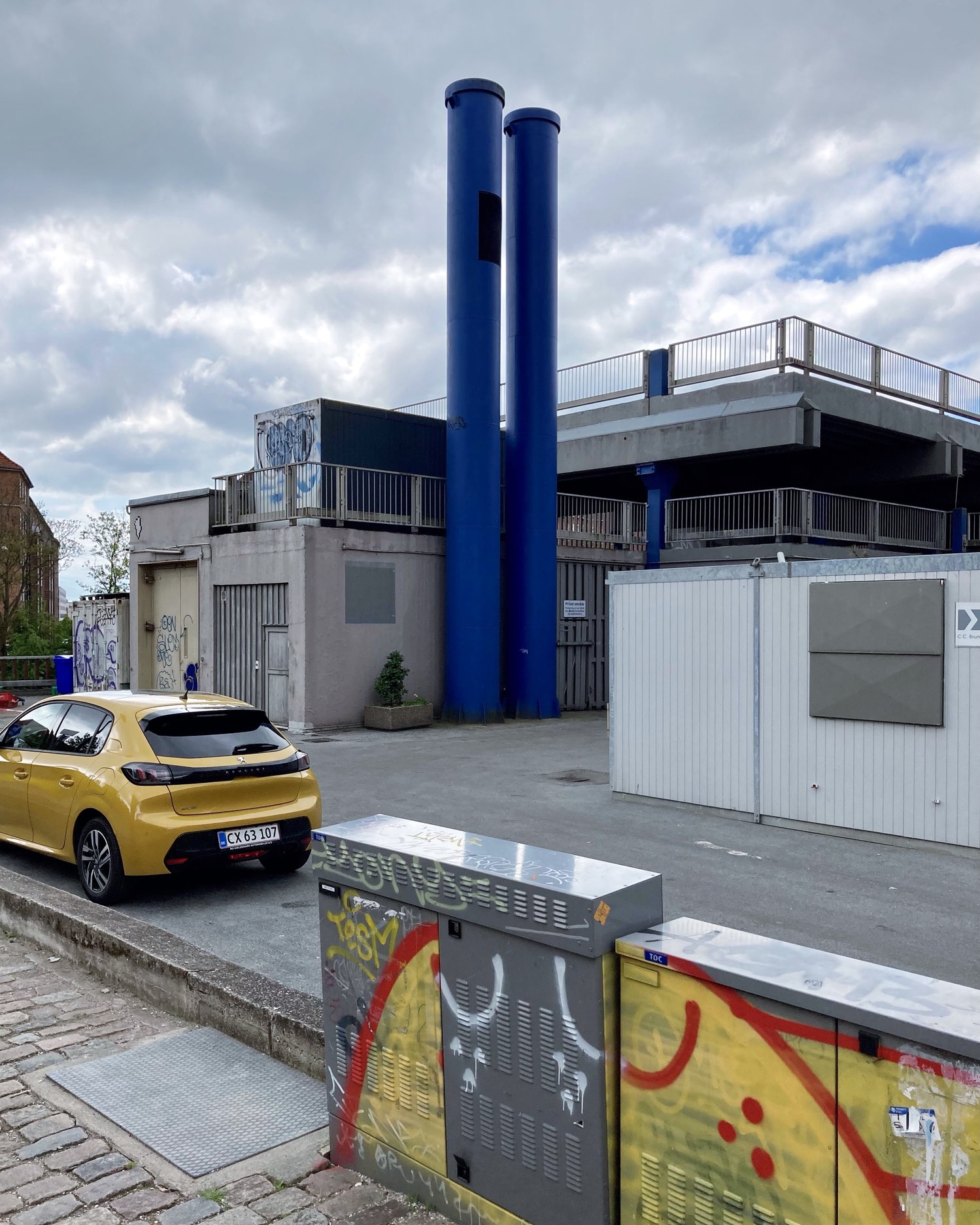 If it wasn't for the bronze-yellow of the car bringing out the yellow of SPYO's graffiti in contrast to the two blue chimneys reaching up against the grey-blue of the sky, I perhaps wouldn't have taken this photograph of what is otherwise a generally drab corner of Valby.