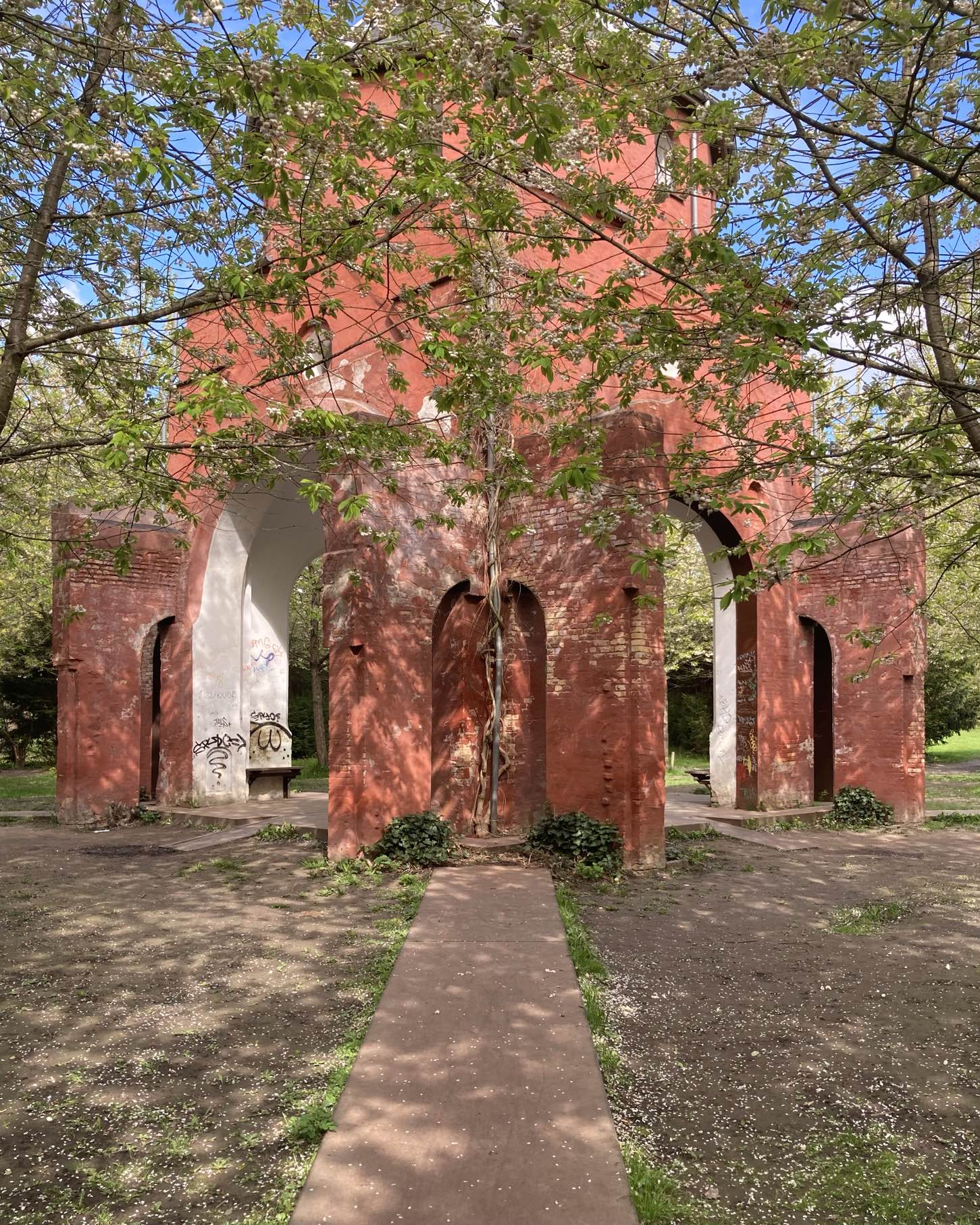 A little Rorschach test with this pavilion, the remains of the West Chapel, converted as part of the Crossroads Project (Stjernevejsprojektet) in the middle of Vestre Kirkegaard. A fresh morning, blossoms sprinkled on the ground. Birds singing. The sounds of nature. And some SPYO graffiti if you look closely.
